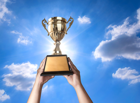 a man holding up a gold trophy cup with bluse sky and sun background copy space ready for your trophy design.