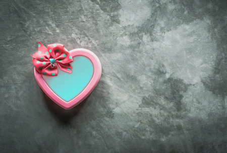cute pink heart gift box on cement board view from above. Stok Fotoğraf