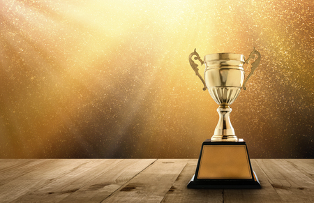 transcend: champion golden trophy on wood table with copy space and gold Twinkly Lights and glitter stars light background copy space ready for your design. Stock Photo