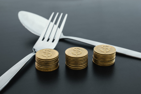 fork and money on dark board business saving money concept.