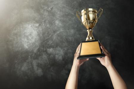 een man die een gouden trofee cup met grunge muur achtergrond kopie ruimte klaar voor uw trofee ontwerp. Stockfoto