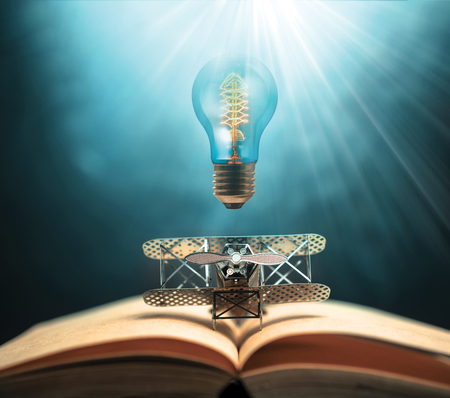 antique edison style filament light bulbs and aircraft figther on open book with abstract light studious student, education, concept. Stock Photo