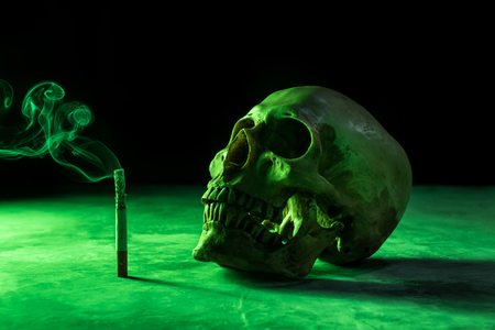 abstract still life Skull of a Skeleton with Burning Cigarette, stop smoking campaign concept with copy space.