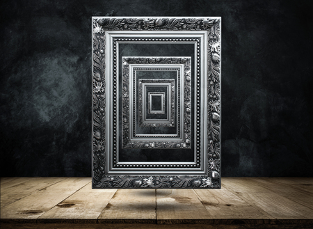 silver Antique picture Frame on dark grunge wall with Wooden table top mysterious, confused, background concept.