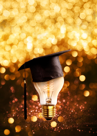 dweeb: congratulations graduates cap on a lamp bulb with glitter lights grunge background.