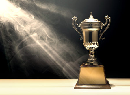 silver trophy placed on wooden table with dark background copy space ready for your design win concept. Stock Photo