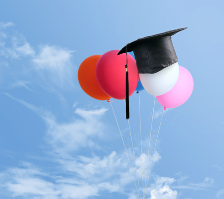 congratulations graduates on top of Balloons with blue sky background.