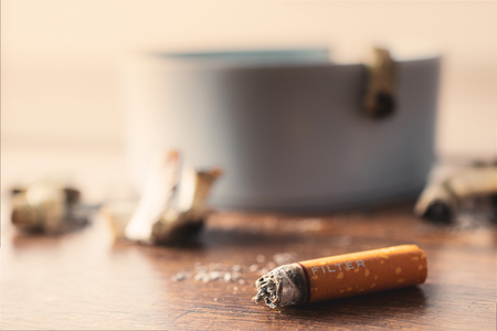 Ashtray with cigarette on wood table.