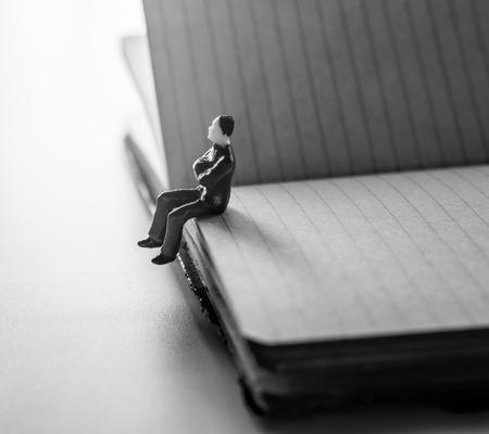 thinking man, miniature man sitting alone on notebook.