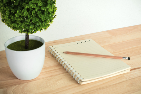 Artificial tree with notebook and pencil on work desk. Stock Photo