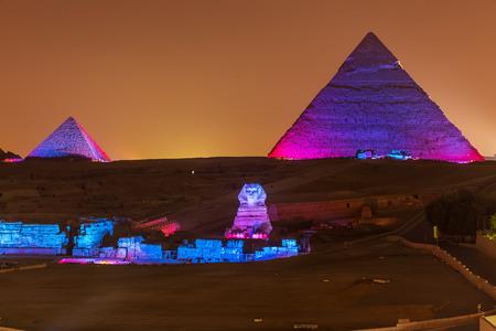 Las pirámides y la Esfinge en las luces de la noche, Giza, Egipto Foto de archivo