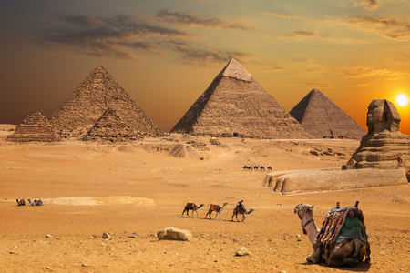 Beautiful sunset view at the Sphinx and the Pyramids of Giza, desert scenery with camels. Banque d'images - 125040379