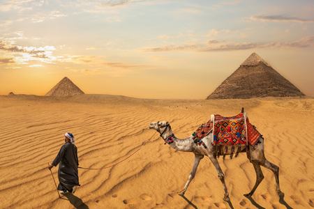 A bedouin with a camel in front of the Pyramid of Khafre and the Pyramid of Menkaure, Egypt Banque d'images - 125044632