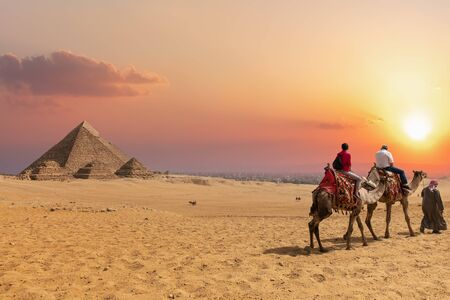 The Pyramid complex of Giza and arabs on camels, Egypt Stock Photo