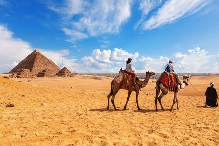 Tourists, camels, bedouins and the Pyramids in Giza desert