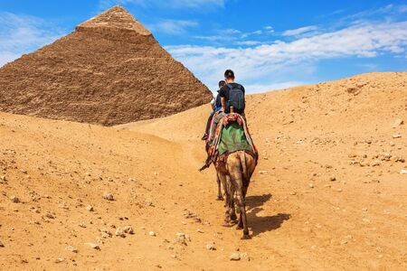 Tourists riding camels near the Pyramid of Khafre, Giza Imagens
