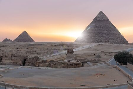 Sunrise in Giza: view on the Sphinx and the Pyramids