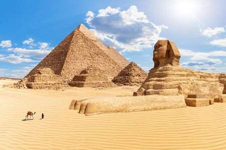 The Pyramids and the Sphinx in the sunny desert of Giza, Egypt.