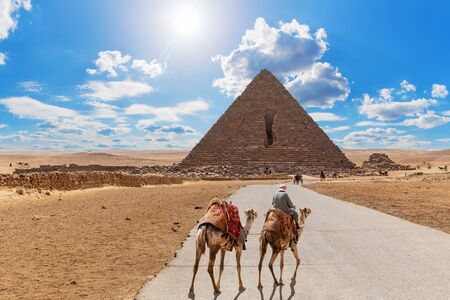 Road to the Pyramid of Menkaure and the bedouin with camels, Giza, Egypt.
