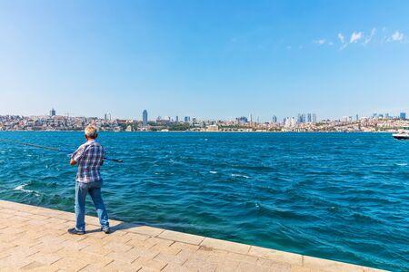 Turkish man fishing in the Bosphorus, Istanbul.