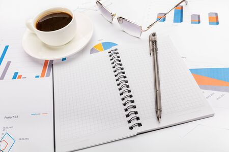 Notepad, a pen, coffee and glasses in business or school concept.