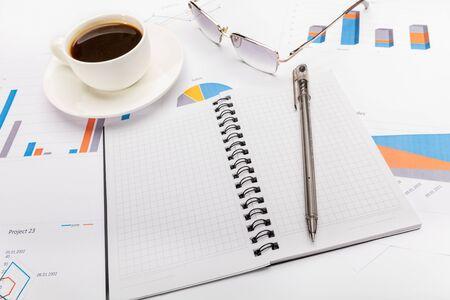 Notizblock, Stift, Kaffee und Brille im Geschäfts- oder Schulkonzept.