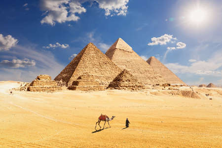 Famous Pyramids of Egypt and a bedouin with a camel, Giza, Cairo