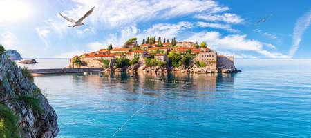 Seagull flies by Sveti Stefan island, wonderful panorama from the rock, Budva riviera, Montenegro