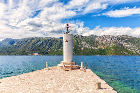 Lighthouse by the Church of Our Lady of the Rocks in the Adriatic sea, Bay of Kotor near Perast, Montenegro.