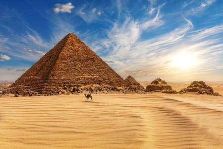 The Pyramid of Menkaure at sunset in Egypt and a camel nearby, Giza