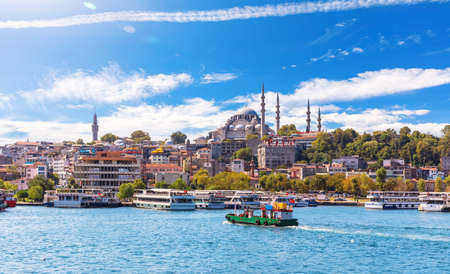 Eminonu Pier with Ships and Suleymaniye Mosque on the background, view from the Golden Horn inlet, Istanbul