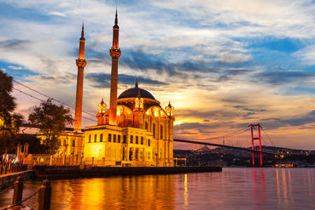 A Grand Imperial Mosque of Istanbul and the Bosphorus bridge in the night lights. 免版税图像