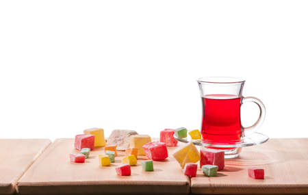 Traditional turkish delight, lokum, and Turkish tea on the wooden table, isolated on a white background