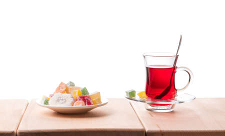 Traditional turkish tea and delight on the wooden table, isolated on a white background.