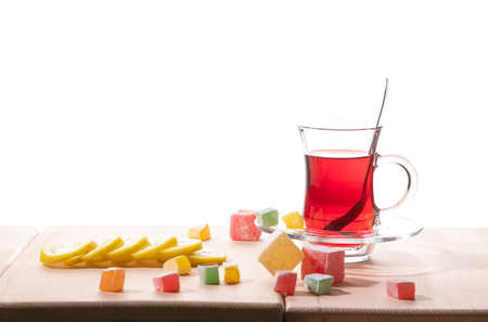 Traditional turkish tea, lemon and delight on the wooden table, isolated on a white background. 免版税图像