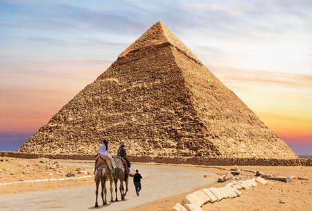 Tourists on camels with bedouin near the Pyramid of Chephren, Egypt 免版税图像