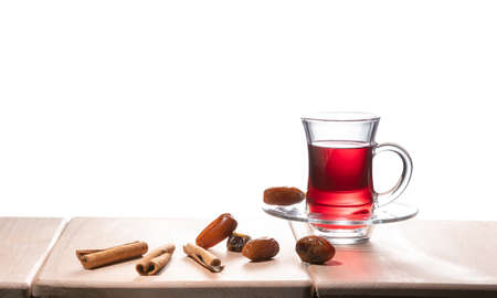 Turkish traditional tea with cinnamon sticks and dates, isolated on white background 免版税图像