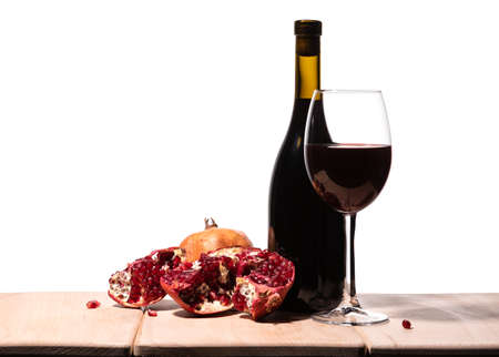 Isolated burgundy red wine bottle, wine glass and juicy pomegranate on white background 免版税图像