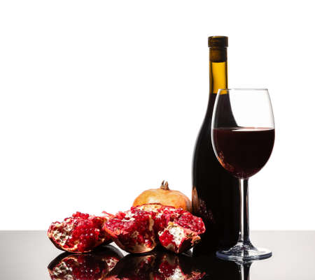 Isolated wine bottle, wine glass and juicy pomegranate on a white background 免版税图像
