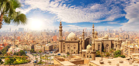 Famous Mosque of Sultan Hassan behind the palm tree, Cairo skyline, Egypt