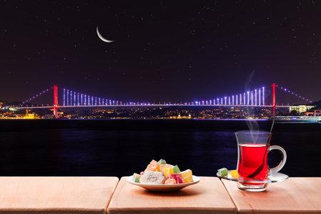 Turkish tea party near the Bosphorus bridge at night, Istanbul, Turkey