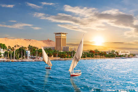 Aswan sunset scenery, view of the Nile and traditional boats, Egypt. 免版税图像