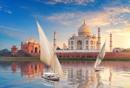 Famous Taj Mahal complex, the Yamuna river and boats, beautiful sunset, Agra, India 免版税图像