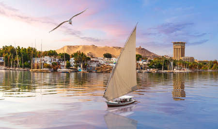 Beautiful view of the Nile river and a sailboat by the city of Aswan, Egypt