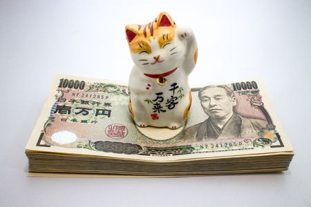 beckoning: Wad of money and a beckoning cat Stock Photo