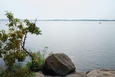 riverside tree: Riverside, lone stone, lonely tree, blue water, blue sky, motorboat far.