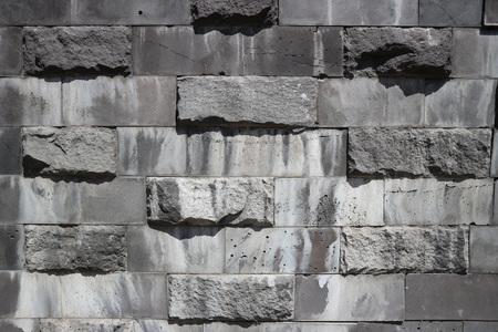 Smooth and untreated gray rectangular granite stone wall, rubblework. Stock Photo