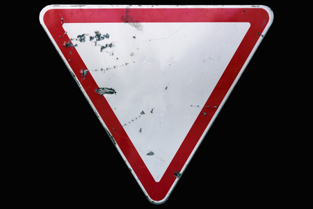 Triangular scratched red border road sign Yield isolated on black. Stok Fotoğraf