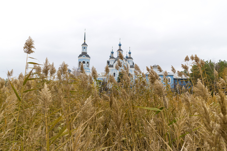 Orthodox church behind a wall of dry cane.