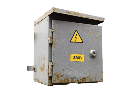 Rusty municipal electrical grey outdoor cabinet with lock and hazard sign isolated on white. Stock Photo